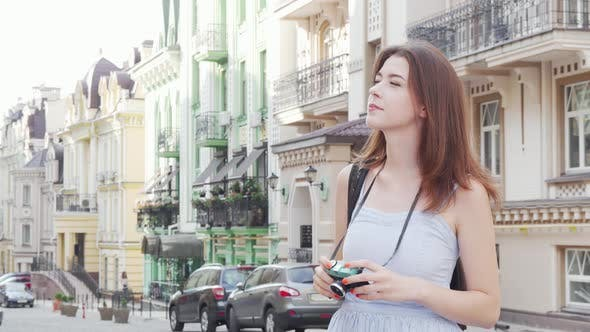 Thumbnail for Beautiful Woman Taking Photos of the City on Her Retro Photocamera