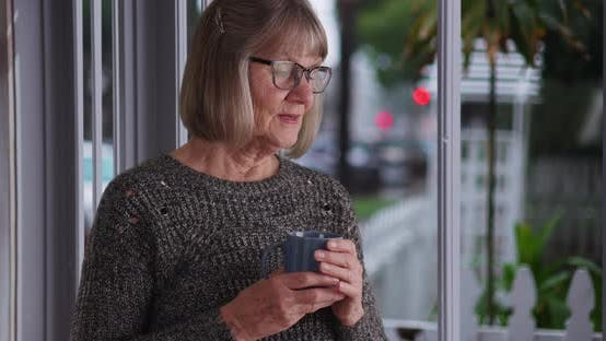 Thumbnail for Serious mature woman holding coffee cup sneezes indoors by window on cold day