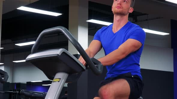 Thumbnail for A Young Fit Man Trains on an Exercise Bike in a Gym - Closeup From Below