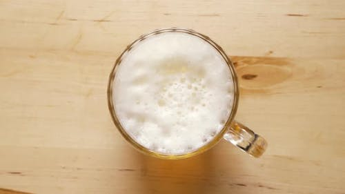 Top View of Pint of Light Beer with Foam on Wooden Table