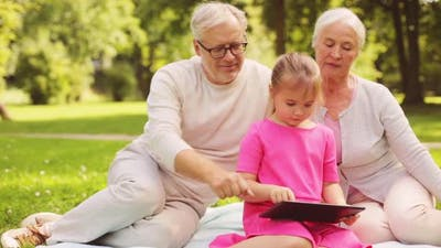 Grandparents and Granddaughter with Tablet