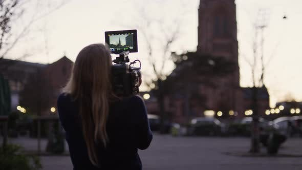 Thumbnail for Female Film Maker Filming Church Tower In City