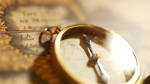 Old vintage compass lying on the ancient map. Used in sailing for navigation.