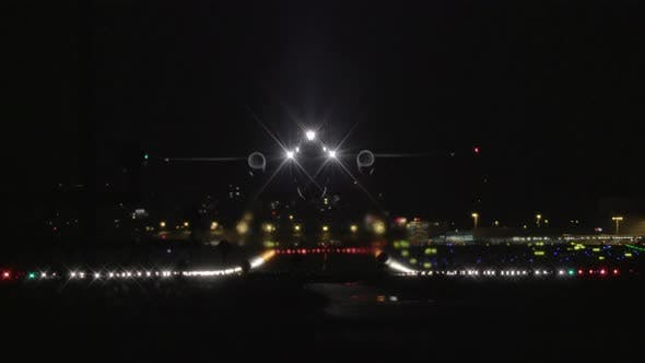 Airplane Taking Off at Night from Airport Runway