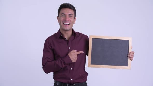 Thumbnail for Young Happy Hispanic Businessman Holding Blackboard and Giving Thumbs Up
