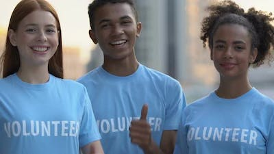 Extremely Happy Multiracial Volunteer Friends Showing Thumbs-Up Camera, Charity
