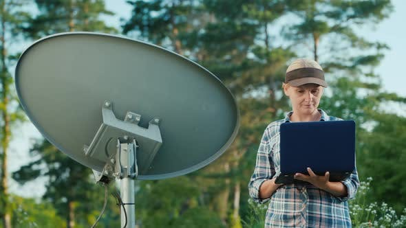 Technician Sets Up a Terrestrial Satellite Dish, Uses a Laptop