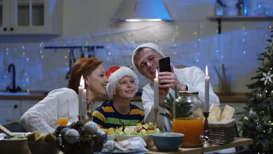 Thumbnail for Family Watching Photos at Christmas Table