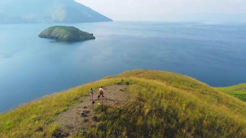 Aerial slow motion: couple tourists hiking on Lake Toba Sumatra Indonesia