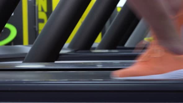 Thumbnail for A Fit Woman Starts To Run on a Treadmill in a Gym - Side Closeup on the Feet