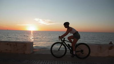 Young motivated woman in top and shorts is cycling on promenade at sunset. Cycling concept