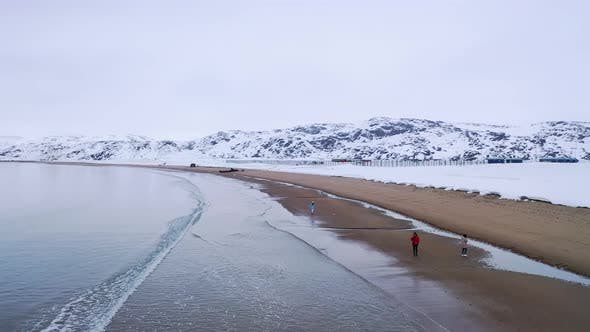 Thumbnail for Travelers walking along shore by water in winter