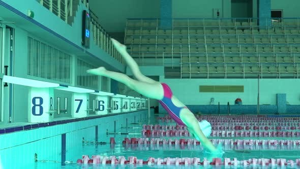 Teenager Girl Swimmer Dive In Swimming Pool. Female Swimmer Dives in Swimming Pool for a Swim