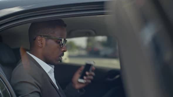 Thumbnail for African Businessman Sitting on Backseat of Taxi