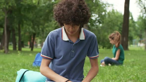 Thumbnail for Teenage Boy with Laptop Outdoors