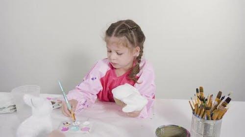Little girl painting paper mache figurine at homeschooling art class.