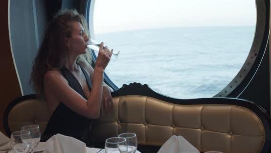 Thumbnail for Selige Frau sitzt allein am Tisch im Restaurant auf Kreuzfahrtschiff, trinkt Champagner.