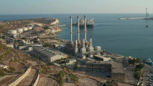 Factory with Three Big Chimneys By the Water on Mediterranean Island Malta