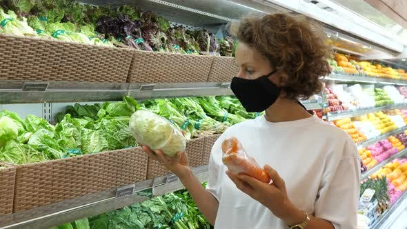 A Woman in a Face Mask Comparing Carefully Pre Packed Vegetables and Chooses the Best Ones