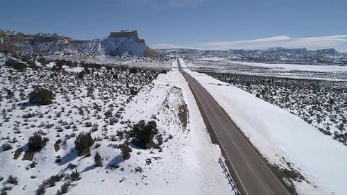Flying along road through the vast snowy landscape in Utah