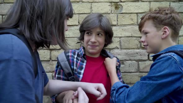 Thumbnail for Portrait of Scared Bullied Boy Fighting with Aggressive Offenders at Wall. Brunette Caucasian