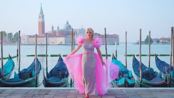 Girl Dressed in Pink in Venice in Front of the Gondolas on the Water