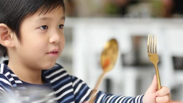 Cute Asian Child Holding A Spoon And Fork With Empty White Plate  In Restaurant