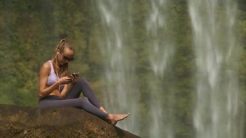 Blond Girl Sits Barefoot on Stone Listens To Music