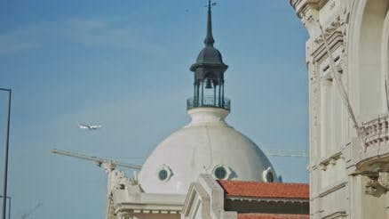 Plane is flying above an old church