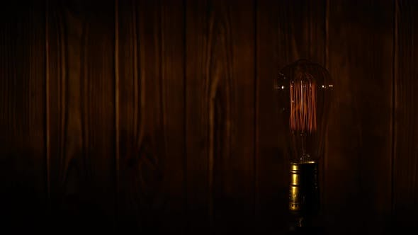 Thumbnail for Old Vintage Edison Light Bulb Glowing on Background of Wooden Planks