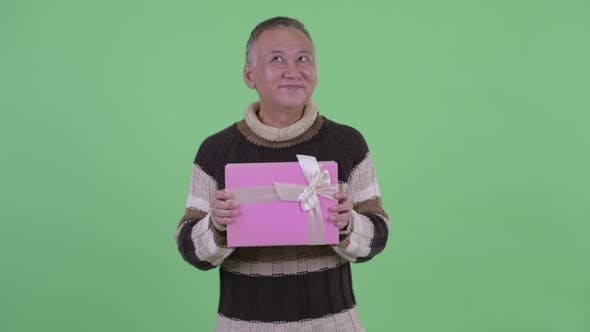 Thumbnail for Happy Mature Japanese Man Thinking While Holding Gift Box