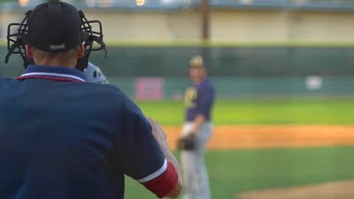 The umpire at a baseball game makes a call.
