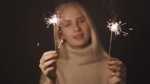 Close Up Sparklers Portrait of Beautiful Caucasian Woman Celebrating New Years Eve Enjoying