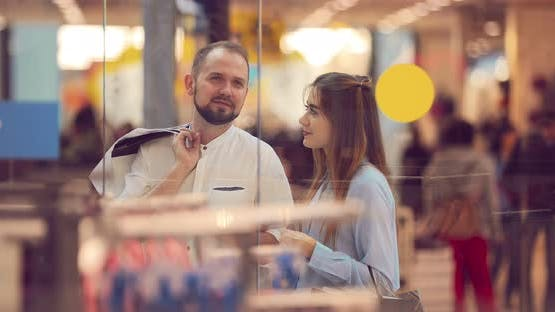 Couple are Standing in a Shopping Center Behind a Shop Window Near the Store and are Discussing