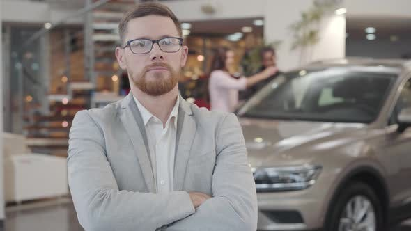 Thumbnail for Portrait of Successful Caucasian Car Dealer Crossing Arms and Gesturing Yes By Shaking Head