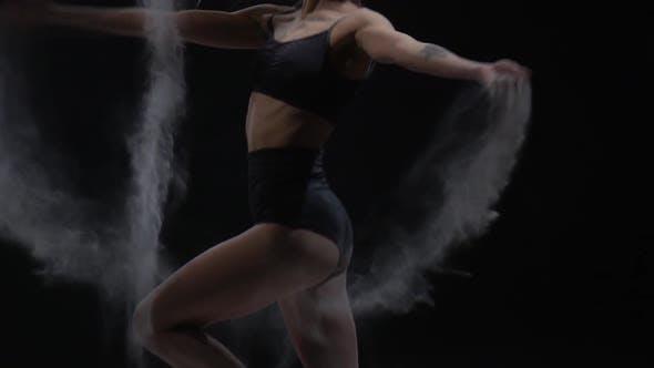 Mädchen mit idealem Körper wirft Staub im Studio auf schwarzem Hintergrund. Zeitlupe