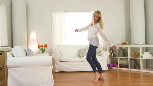 Thumbnail for Mature woman jumping on couch and dancing in living room