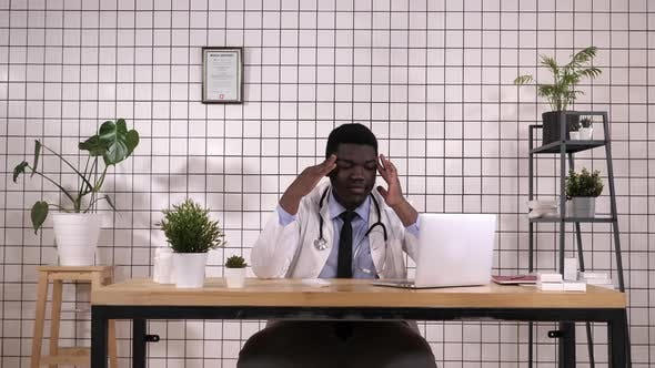 Thumbnail for Young African American Doctor Suffering From Headache Desperate and Stressed Because Pain