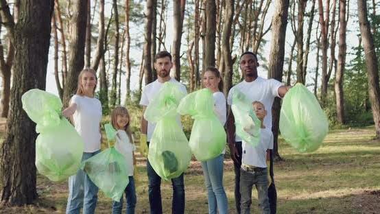 Mixed Race Naturliebhaber posieren auf der Kamera mit Plastiktüten mit Müll