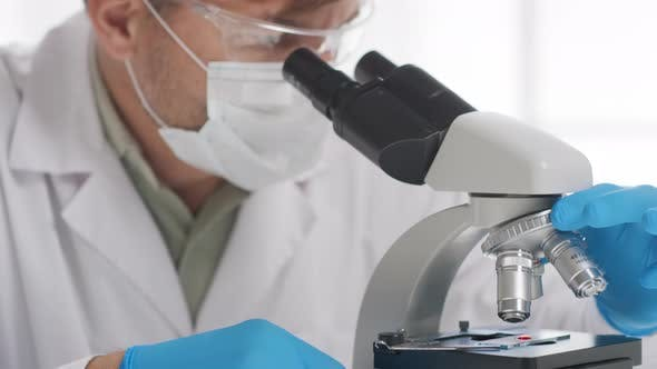 Thumbnail for Male Biomedical Scientist Looking into Microscope