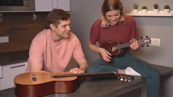 Young People Entertain Each Other Sitting at Home on Self-isolation. A Married Couple Plays the