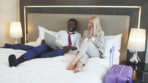 Beautiful Diverse Couple Lie on Bed with Laptop