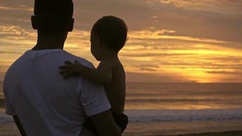 Dad and Little Boy Enjoying Sunset on Ocean