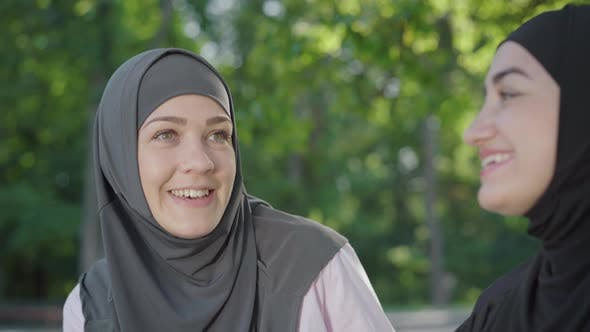 Thumbnail for Joyful Young Muslim Woman with Hazel Eyes Talking with Friend and Laughing. Portrait of Cheerful