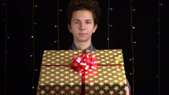 Boy with a Gift Box on Black Background. Gift Box with Ribbon for Happy New Year, Merry Christmas