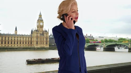 London businesswoman making urgent phone call to her client