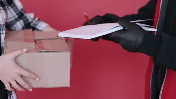 Woman in a Mask Is Receiving a Parcel From a Deliveryman and Signing a Document