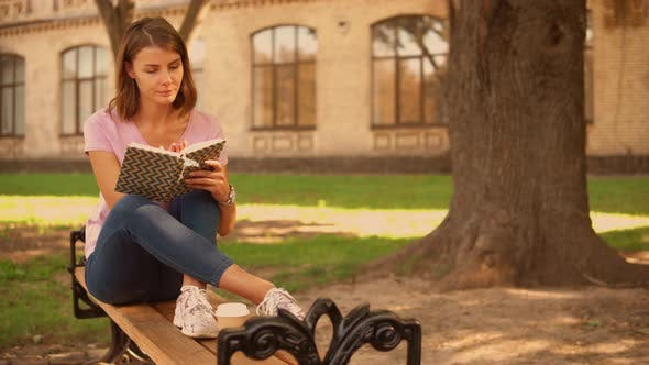 Young Woman Studying Near College