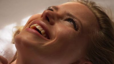 Smiling Blonde Model Lying on Bed