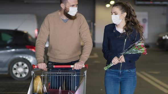 Video of couple in protective mask coming back from shopping. Shot with RED helium camera in 8K.